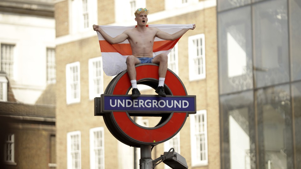 An England soccer fan sits with England's Saint George's Cross flag atop a London Underground subway sign.