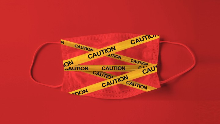 An illustration of a face mask with caution tape over it.