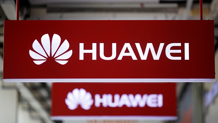 Huawei signs hang from a ceiling.