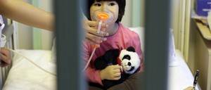 A toddler breathes from a nebulizer while sitting in a crib.