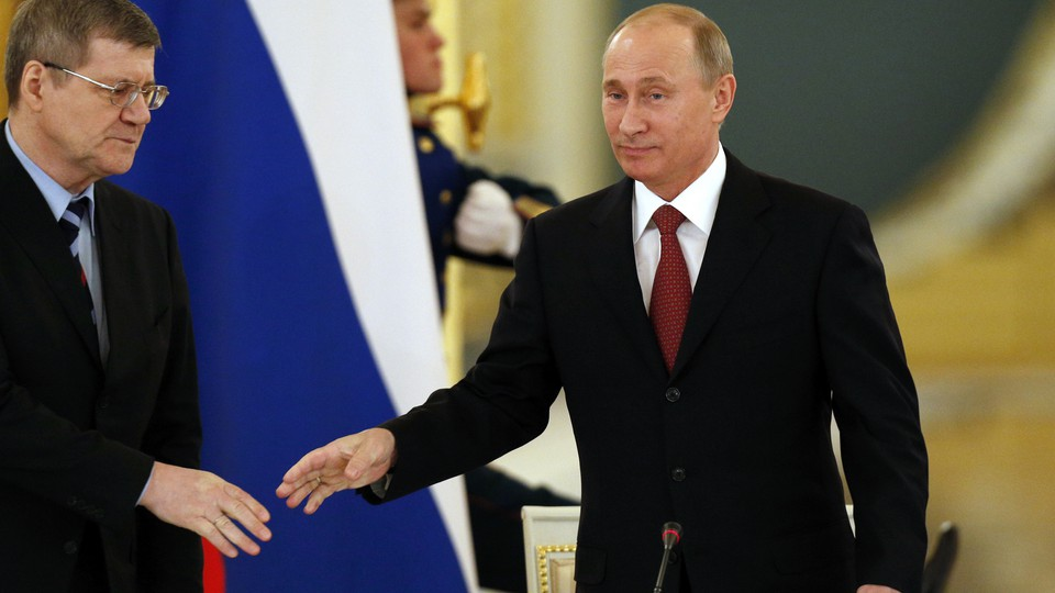 Russian President Vladimir Putin (R) greets Prosecutor General Yury Chaika as he arrives for a meeting with regional officials in the Kremlin in Moscow January 31, 2013.