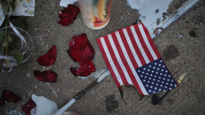 A candle, rose petals, and a partially intact American flag lie on a sidewalk