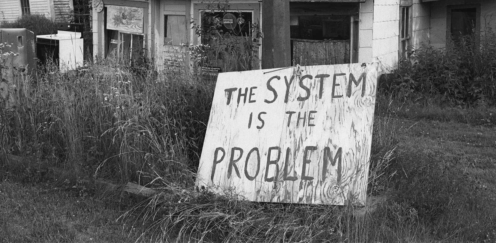 "Black and white photo of ruined house with hand-painted sign ""The System Is the Problem"""