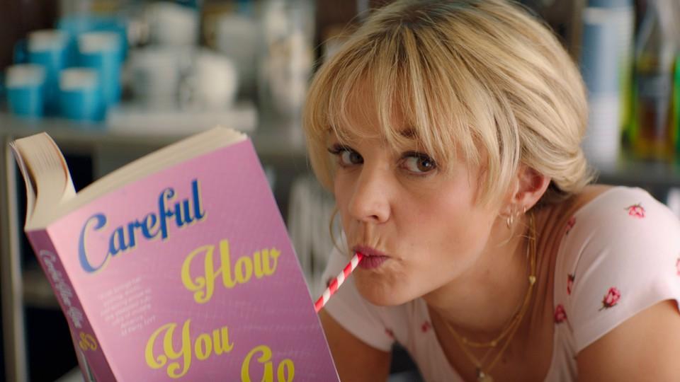 Film still of Carey Mulligan reading a book