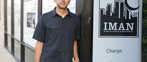 Rami Nashashibi stands in front of a sign for IMAN, his organization.