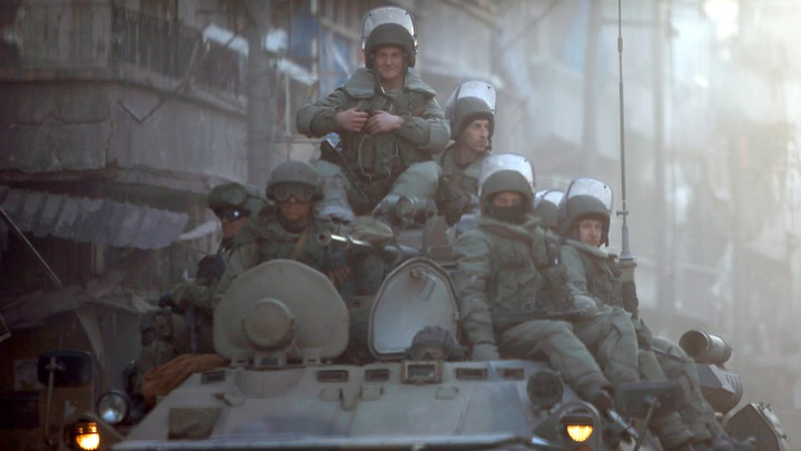 Heavily armed Russian soldiers ride atop an armored tank in Aleppo.