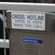 "A metal box with a red button that says ""push to call,"" and a placard reading ""Crisis Hotline. There is hope make the call"""