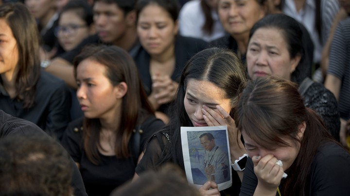 A Thai woman wipes away tears as she holds a picture of the late King Bhumibol Adulyadej.