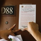 A person tapes an eviction notice to the door of an apartment.