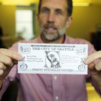 """The author of Seattle's """"democracy voucher"""" initiative holding up a $25 voucher."""