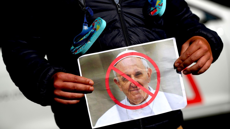 A protester in Dublin holds a picture of Pope Francis during a demonstration against clerical sex abuse.