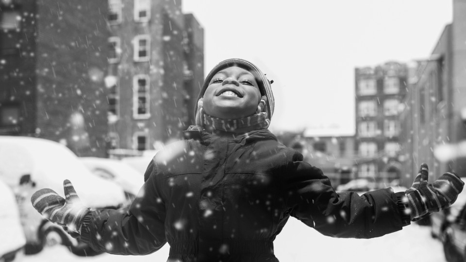 A girl lifts her face to the sky as snow falls.