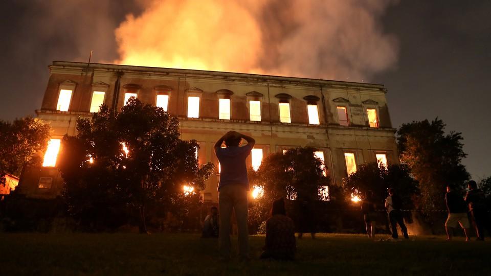 Outside spectators watch the National Museum in Rio de Janeiro burn.
