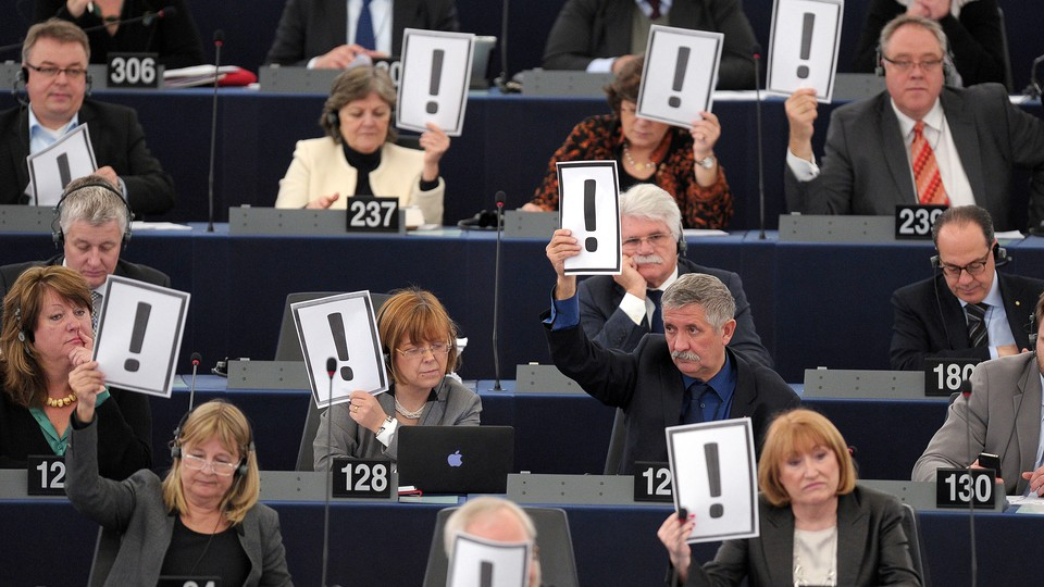 Men and women hold placards bearing an exclamation mark