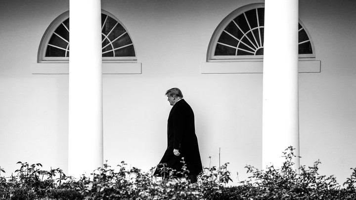 President Trump walks in front of the White House.