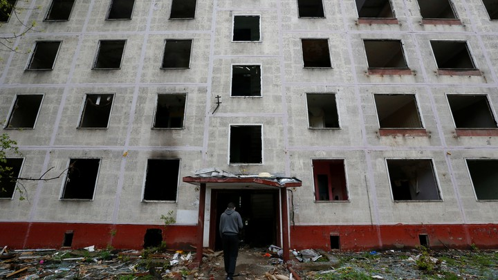 A worker passes a building, which is part of the old five-story apartment blocks demolition project launched by the city authorities, in Moscow, Russia.