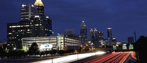 Traffic moving along Interstate 75 against the downtown skyline in Atlanta.