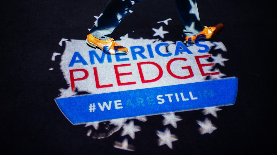 """Two feet are shown walking on an """"America's Pledge"""" logo"""