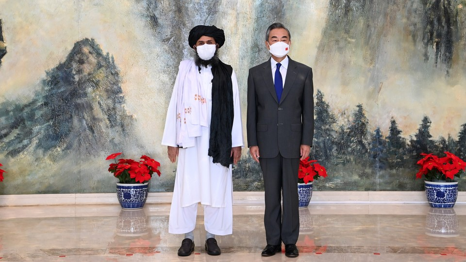 A masked Taliban official stands next to a masked Chinese official.