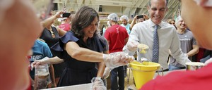A photo of the two mayors using ladles to pack lunches.