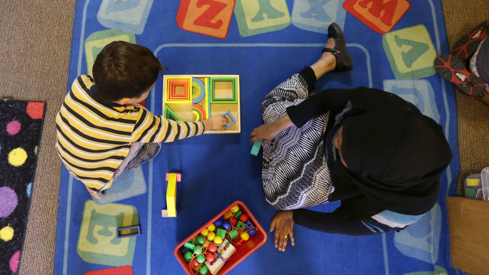 An overhead shot of a child playing with blocks on a blue carpet with an adult.