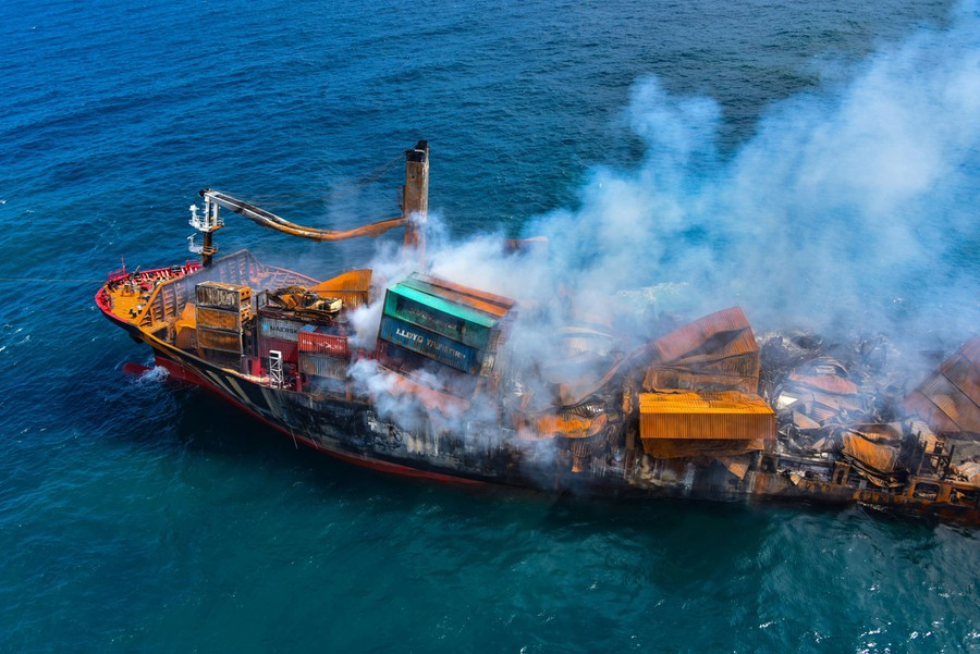 A severely damaged and smoking cargo ship is seen at sea.