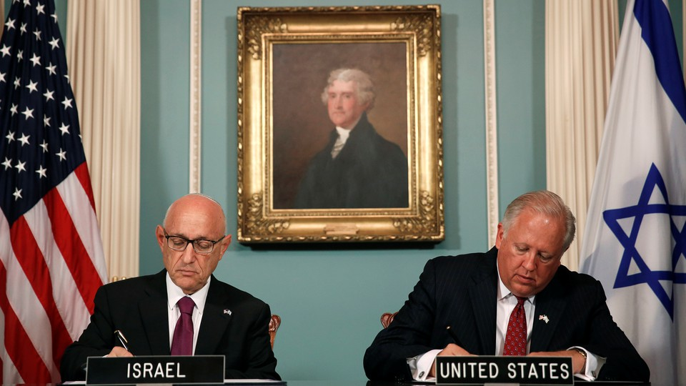 U.S. and Israeli officials sign an unprecedented military-spending deal in Washington, D.C. on September 14, surrounded by a portrait of Thomas Jefferson and American and Israeli flags.