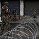 Indian security forces stand near concertina wire.