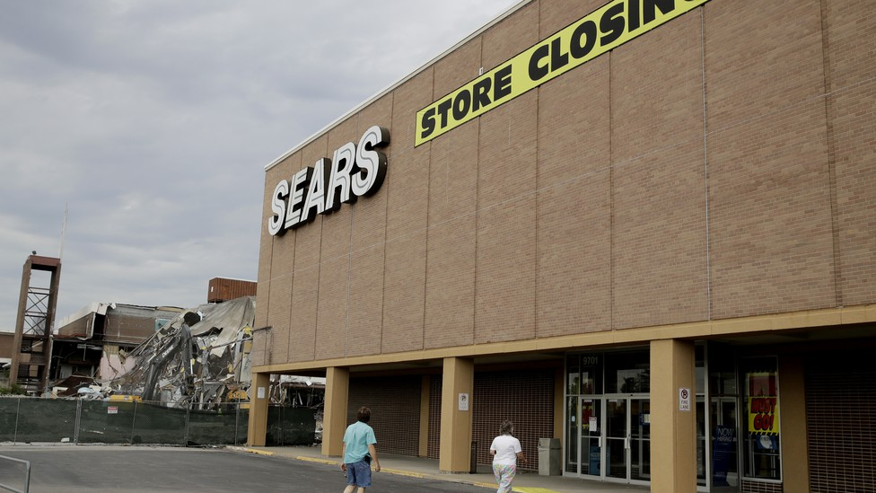 Two people walking into a Sears store that is slated to close