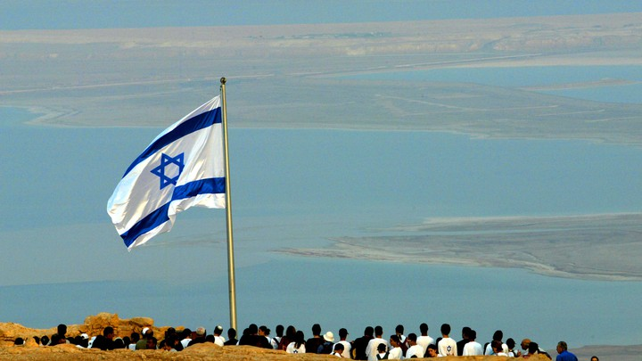 The Israeli flag flies on the ancient hill top fortress of Masada in the Judean desert