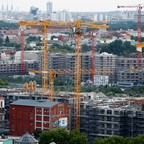 Cranes build new buildings in Berlin, Germany.