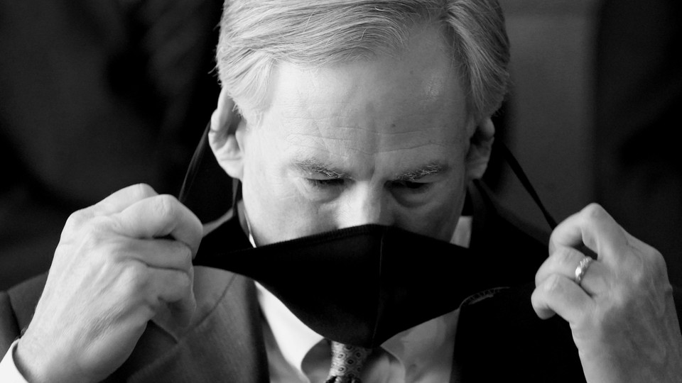 A black and white photo of Greg Abbott taking a mask off.
