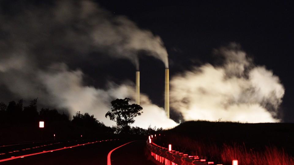 Smokestacks releasing plumes at night