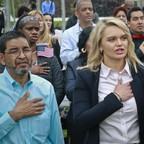 Immigrants sing the national anthem during a naturalization ceremony.
