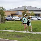 Two girls walk past a school