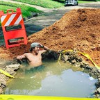 A man soaking in a hot tub made from a giant pothole on a street, surrounded by dirt and construction tape