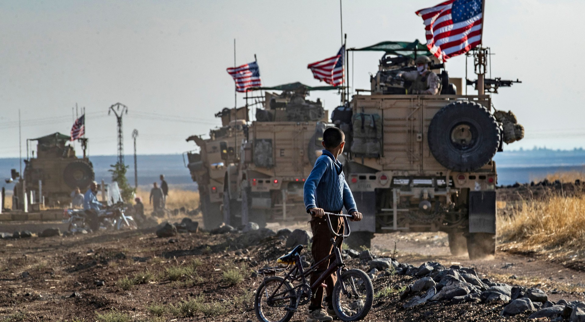 A Syrian boy on a bicycle watched a convoy of US armored vehicles drive away on a dirt road in northeastern Syria.