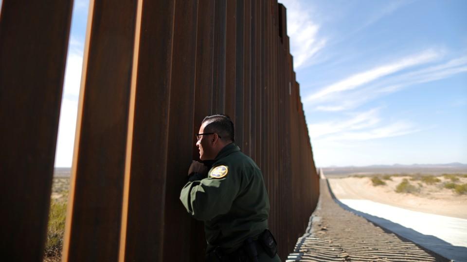 A U.S. Border Patrol agent looks through the U.S.-Mexico border fence in Santa Teresa, New Mexico.