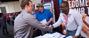 Two men shake hands across a table at a job fair.