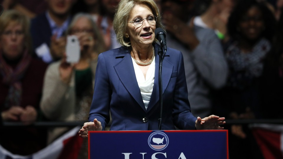 Betsy DeVos stands at a podium.