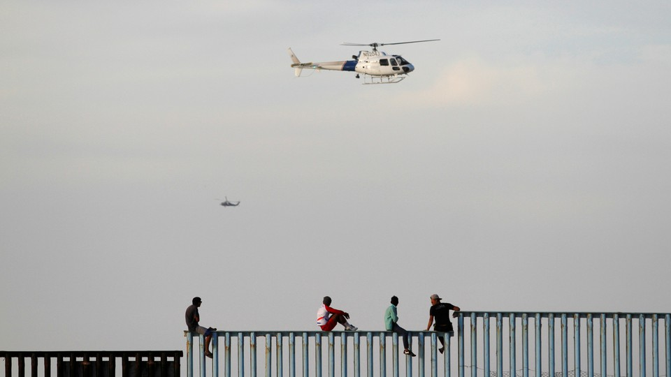 Immigrants sit on a border fence between the United States and Mexico after arriving as part of a caravan.