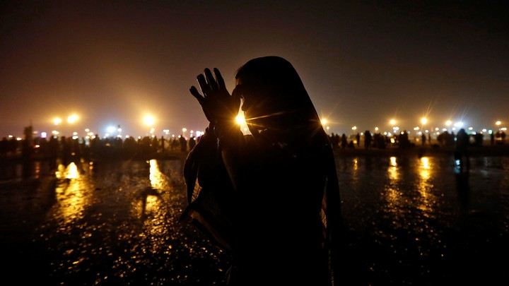 A Hindu pilgrim offers prayers after taking a dip in the Ganges river.