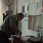 Ivan Fransuzov, the postman of Great Dervent, stamps papers in an office.