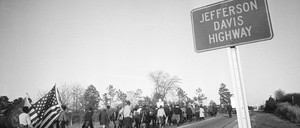 People march along a road as a sign for the Jefferson Davis Highway stands in the foreground
