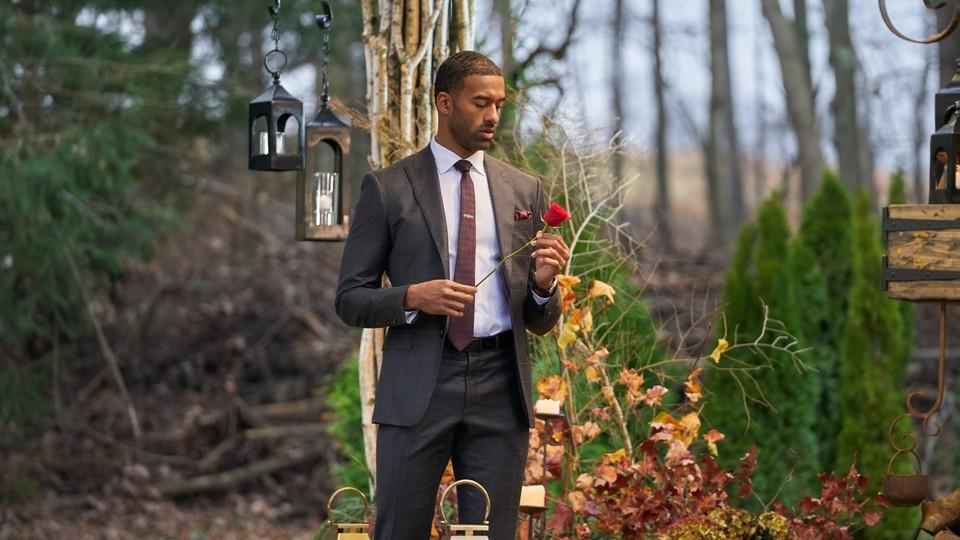 Matt James, the latest Bachelor, looks at a rose