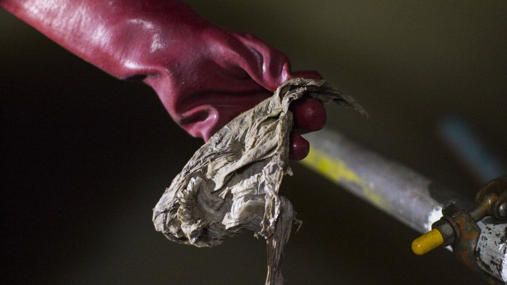 A gloved hand holding a wet wipe found in the Northern Outfall Sewer, London