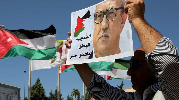 Protesters hold up photos of Jordanian writer Nahed Hattar outside the Jordanian Prime Ministry in Amman, Jordan.
