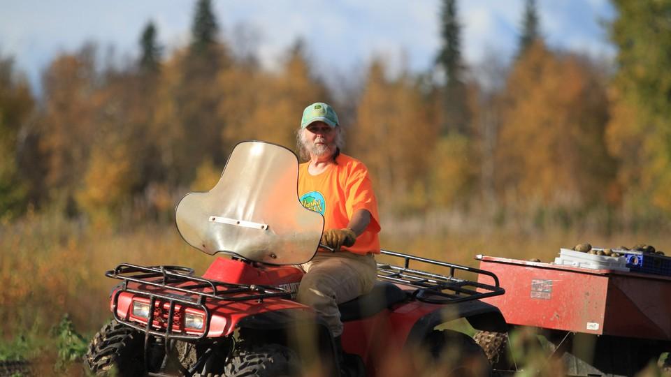 A farmer rides a tractor through a field.