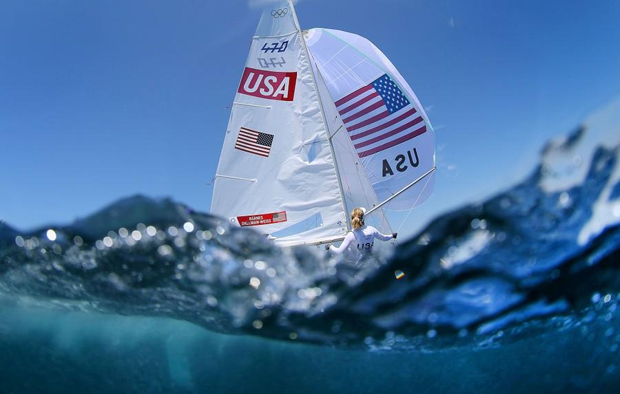 Sailors race in a harbor.