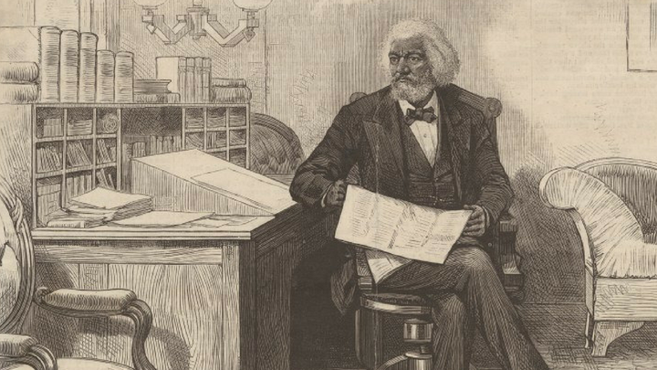 An illustration of Frederick Douglass sitting with a writing box atop his desk